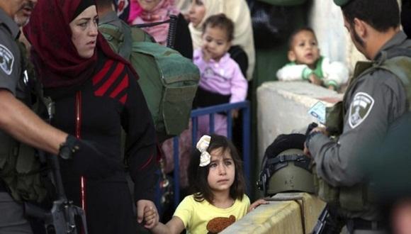 Una niña palestina mira al soldado israelí que revisa las identificaciones de las mujeres palestinas que quieren cruzar el paso de control de Belén, al sur de Jerusalén. Foto: EFE.