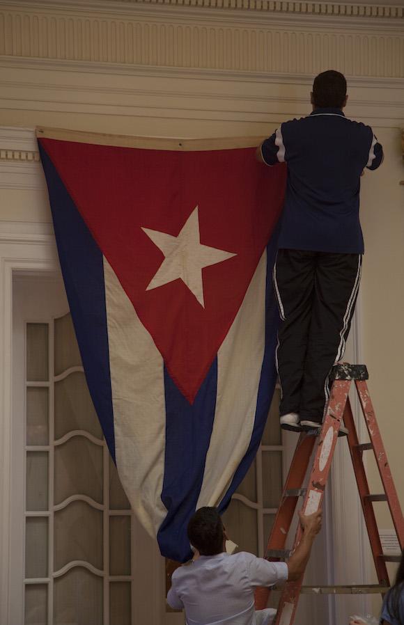 Momento en que un trabajador de la Embajada colocaba la bandera en el segundo piso del edificio, frente al salón donde celebrará la ceremonia oficial de este lunes. Foto: Ismael Francisco/ Cubadebate