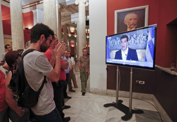 El primer ministro griego, Alexis Tsipras, afirmó que su Gobierno reiniciará mañana las negociaciones con los acreedores para tratar de alcanzar un acuerdo y señaló que la prioridad es la reapertura de los bancos. En la imagen, partidarios del 'no' durante la intervención de Tsipras en televisión. Foto: JEAN-PAUL PELISSIER (REUTERS)