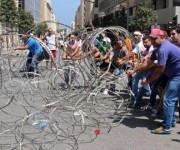 Activistas libaneses intentan quitar el alambre de púas que bloquea la entrada al Palacio de Gobierno del Líbano. Foto: EFE.