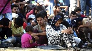 Inmigrantes esperan en una estación de trenes cerca de la ciudad de Gevgelija (Macedonia)