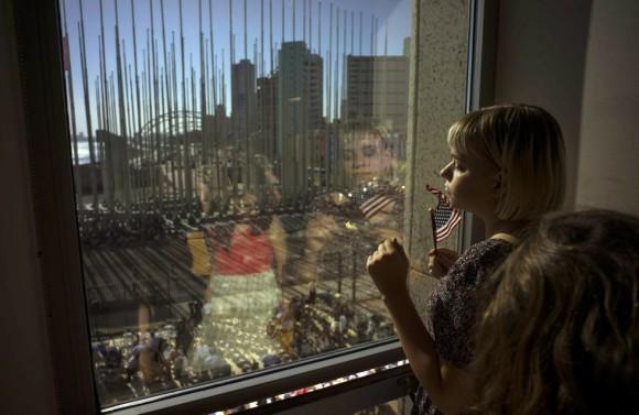 Una niña contempla desde una ventana cómo preparan el escenario donde tendrá lugar la ceremonia en la que John Kerry izará la bandera norteamericana en la embajada de EE UU en La Habana. Foto: AP.