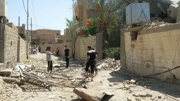 Personas se reúnen frente a un edificio destruido tras un ataque aéreo de la Fuerza Aérea Israelí en la ciudad tomada por militantes del Estado Islámico de Fallouja, oeste de Bagdad. Foto: Xinhua