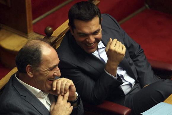 Tsipras (dcha), conversa con el ministro de Economía, Infraestructura, Comercio y Turismo, George Stathakis (izda), durante la sesión parlamentaria en Atenas. Foto: EFE (Tomada de 20minutos.es)