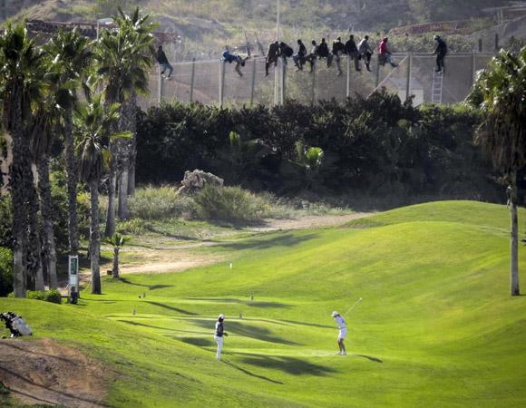 Un grupo de personas sobre la valla de Melilla (José Palazón Reuters)