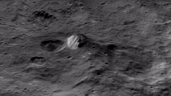 En estas fotografías sin precedentes y las más cercanas hasta el momento, se puede apreciar una montaña de forma cónica y varios cráteres, han revelado este martes medios de comunicación.  Foto: NASA
