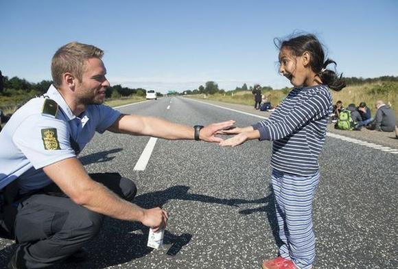 Un policía danés habla con una niña siria migrante. Foto: Reuters