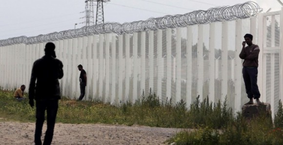 """Varios inmigrantes llaman por teléfono cerca de una cerca con alambre de púas, junto al campamento improvisado llamado """"La nueva jungla"""" en Calais, Francia.- REUTERS / Regis Duvignau"""