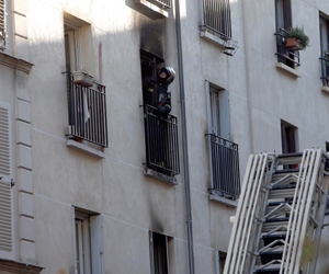 French firefighters inspect an apartment building in which a fire broke-out overnight in central Paris