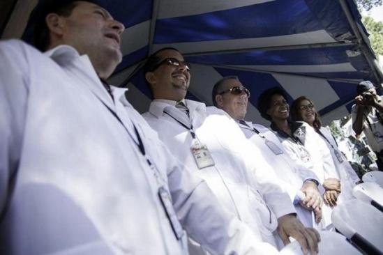 Médicos cubanos en Haití participan en una ceremonia en la estación de la Guardia Costera Almirante Killick durante la apertura de una misión humanitaria del Buque Hospital de la Marina de Estados Unidos, NS Comfort, el 11 de septiembre de 2015, en Puerto Príncipe. Foto: Pierre Michel Jean, AFP