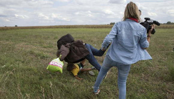 Imágenes grabadas por otros periodistas muestran cómo la reportera húngara hace tropezar a un refugiado que corre con un niño en brazos y cómo estos caen al suelo. Foto: Reuters.