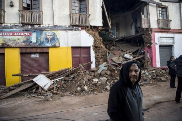 Un hombre pasa frente a una casa completamente destruída por el terremoto. Foto: Getty Images.