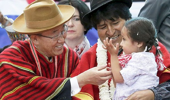 "U.N. Secretary-General Ban Ki-moon and Bolivia's President Evo Morales interact with a girl during the inauguration of a sports arena called ""Coliseo Ban Ki-Moon"" in Vila Vila"