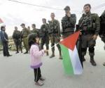 Una niña palestina mueve su bandera enfrente de soldados israelíes. Foto: EFE