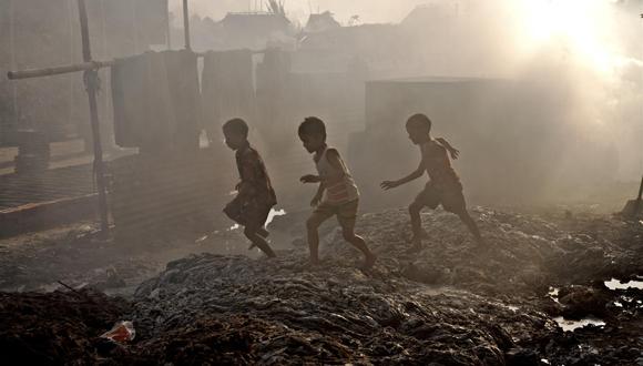 Los niños juegan fuera de su casa que se ha convertido en un gran vertedero de residuos de las industrias de cuero en Bangladesh. Foto: Unicef