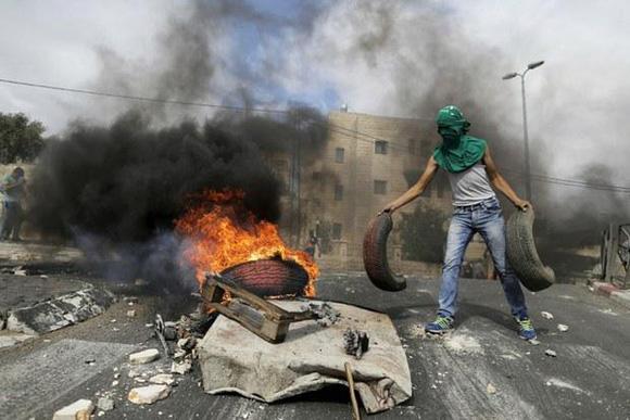 Un joven palestino enmascarado añade llantas a la hoguera, durante los enfrentamientos con la policía israelí este miércoles, en el este de Jerusalén. Foto: Reuters.