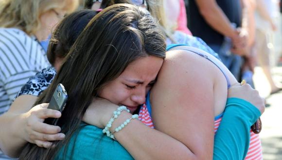 Familiares y amigos se consuelan entre sí luego de la tragedia en un centro educacional de Oregon. Foto: AP.