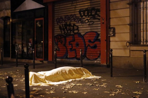 A victim under a blanket lays dead outside the Bataclan theater in Paris, Friday Nov. 13, 2015. Well over 100 people were killed  in a series of shooting and explosions. French President Francois Hollande declared a state of emergency and announced that he was closing the country's borders. (AP Photo/Jerome Delay)