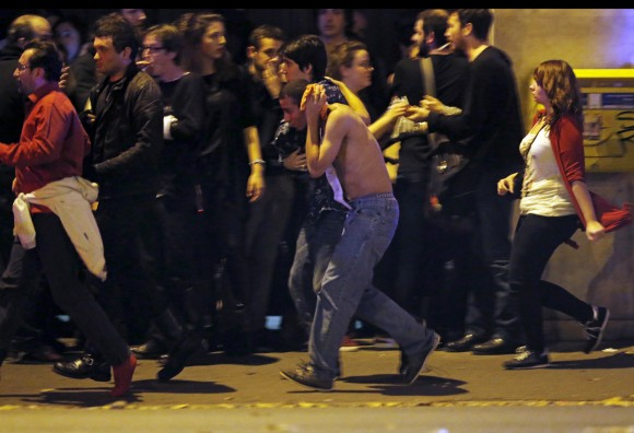 An injured man holds his head as people gather near the Bataclan concert hall following fatal shootings in Paris, France