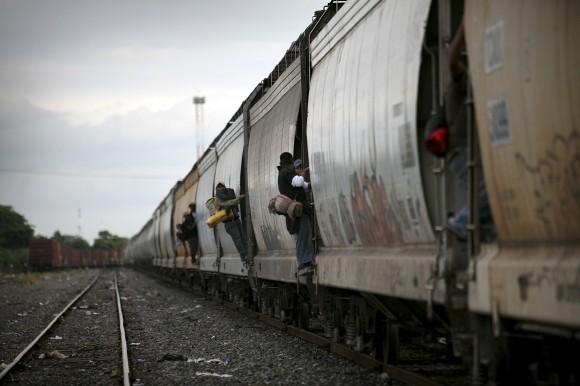 """Migrantes a bordo de """"La Bestia"""" atraviesan Tierra Blanca, Veracruz, en su viaje hacia Estados Unidos. Mujeres, hombres y niños para quienes no existe la Ley de Ajuste Cubano. Foto: Félix Márquez/ Cuartoscuro."""