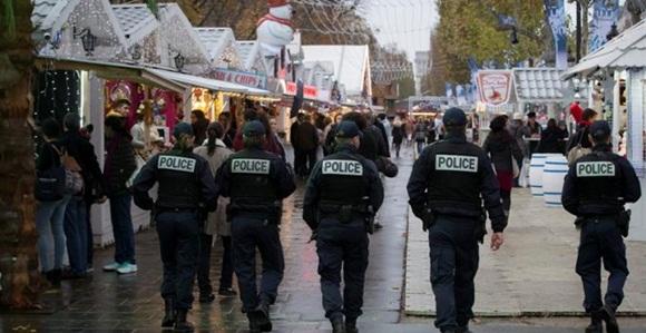 Miembros de la policía patrullan un mercado navideño en la Avenida Campos Elíseos en París. Foto: EFE.
