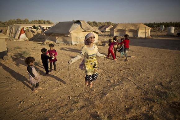 19 de julio, Zubaida Faisal, refugiada siria de 10 años de edad, salta en un asentamiento informal en las afueras de Mafraq, Jordan. Foto: Muhammed Muheisen/AP.