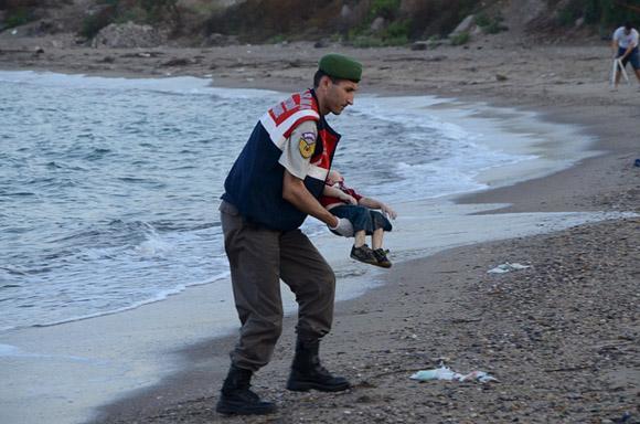 2 de septiembre, un oficial de policía turco lleva a Alan Kurdi, quien se ahogó en un fallido intento por navegar de Turquía a la isla griega de Kos. Foto: Nilufer Demir/Reuters.