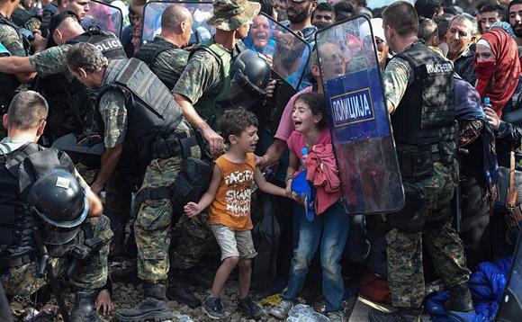 21 de agosto, niños lloran mientras migrantes y refugiados que intentan cruzar a Macedonia por la frontera con Grecia se enfrentan a la policía. Foto: Georgi Licovski/EPA.