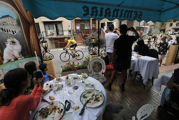 23 de julio, la gente observa a Chris Froome desde la terraza de un restaurante durante el Tour de Francia. Foto: Christophe Ena/AP.