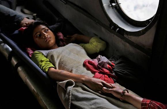 27 de abril, una niña nepalí dañada por el terremoto sostiene la mano de su madre dentro de un helicóptero de la fuerza india. Foto: Altaf Qadri/AP.