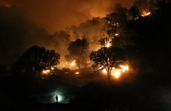 3 de agosto, la silueta de un bombero es visible por la lámpara de su cabeza en la batalla contra el llamdo Fuego de Rocky cerca de Crearlake, California. Foto: Justin Sullivan/Getty Images.