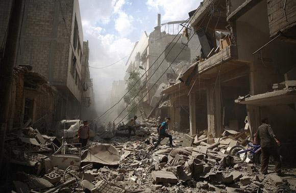 30 de agosto, ciudadanos sirios caminan en medio de los escombros de los edificios destruidos por los ataques aéreos en Douma. Foto: Abd Doumany/AFP.