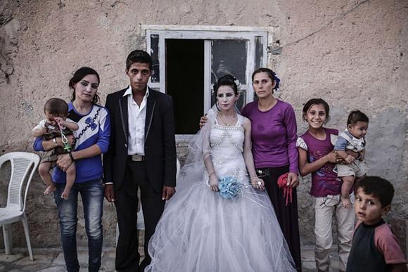 6 de septiembre, una pareja recién casada posa en su hogar con su familia en Kobane, Siria. Foto: Yasin Akgul/AFP.