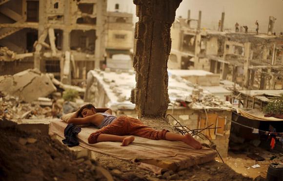 8 de septiembre, un niño palestino duerme en un colchón en los restos de la casa de su familia. Foto: Suhaib Salem/Reuters.