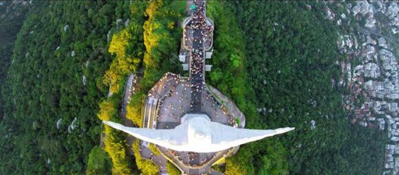 """Alexandre Salem captó esta foto desde su dron en lo alto de la estatua del Cristo redentor en Río de Janeiro, Brasil. """"Una de mis actividades favoritas es llevarme el dron cuando hago caminatas senderistas. Ese día, después de una caminata de dos horas, llegué a los pies de la estatua del Cristo redentor. La noche y el sol ocultándose detrás de la estatua creó la combinación perfecta para esta foto"""", dijo Salem."""