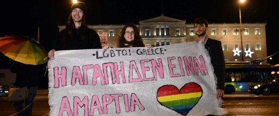 Gay rights activists and members of the Athens LGBT community hold a banner reading in Greek 'Love is not a sin' outside the Greek parliament in Athens on December 22, 2015 as parliament votes on granting same-sex couples the right to a civil union, despite strong opposition from the influential Orthodox church.  Greek government is seeking to meet its obligations after it was condemned for anti-gay discrimination by the European Court of Human Rights in 2013. / AFP / LOUISA GOULIAMAKI