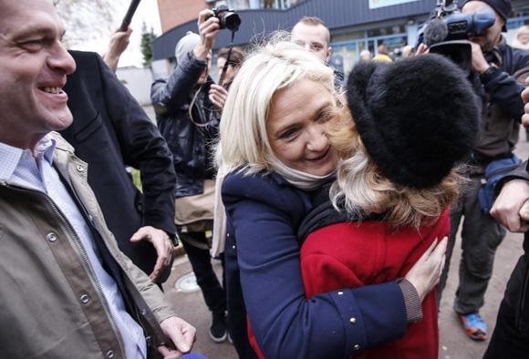 Marine Le Pen abraza a una partidaria, ayer, tras depositar su voto en las regionales francesas, en Henin-Beaumont. Foto: Julien Warnand/EFE.