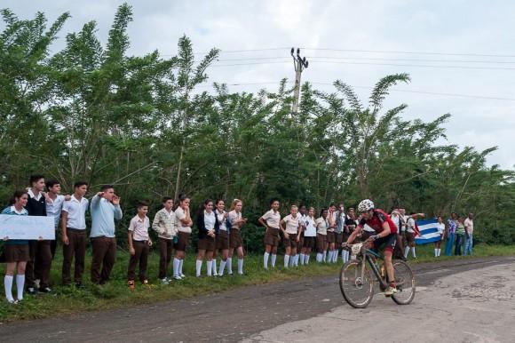 Estudiantes cubanos animan la carrera de Francisco Salamedo durante la tercera etapa Soroa-Viñales (119 km) de la Titán Tropic Cuba de ciclismo de montaña el martes 8 de diciembre de 2015. FOTO de Calixto N. Llanes.