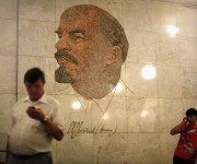 Men use their mobile phones as they stand in front of a mosaic depicting former Soviet leader Vladimir Lenin at Biblioteka Imeni Lenina metro station in Moscow