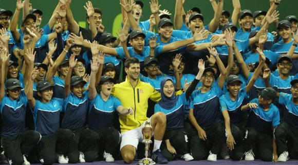 Novak Djokovic posa con decenas de chicos y chicas que colaboraron en el Qatar Open tennis el 9 de enero del 2016, en Doha. Karim Jaafar AFP