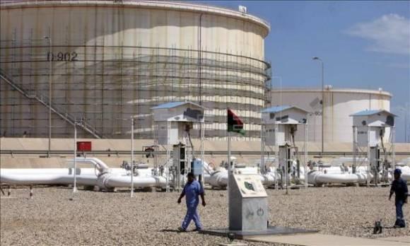 Varios trabajadores caminan en las inmediaciones de la refinería de petróleo de Zawiya, a unos 40 km de Trípoli, Libia. Foto: EFE.