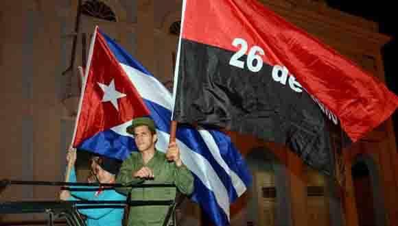 Jóvenes integrantes de las Fuerzas Armadas Revolucionarias (FAR), portan la Bandera Cubana y la del 26 de Julio, durante la reedición de la entrada a La Perla del Sur, hace 57 años, de la Caravana de la Libertad, en Cienfuegos, Cuba, el 6 de enero de 2016.   ACN FOTO/ Modesto Gutiérrez Cabo