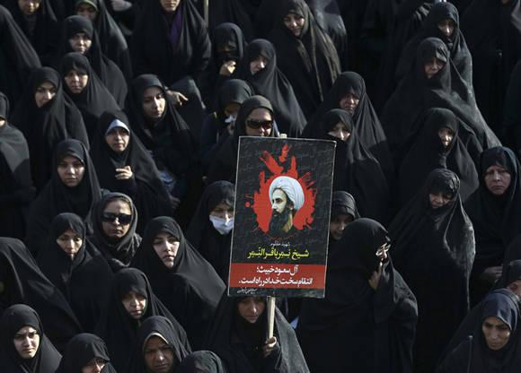 Una mujer iraní sostiene un cartel que muestra a Sheikh Nimr al-Nimr, lunes, 4 de enero de 2016. Foto: Vahid Salemi/AP.