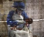 sobreviviente del Ébola, consuela a una niña en Paynesville, Liberia. Foto John Moore