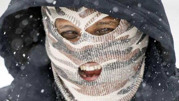 Un hombre enmascarado camina bajo la nieve en una calle de la ciudad de Alexandria, en el estado de Virginia. Foto: AP.