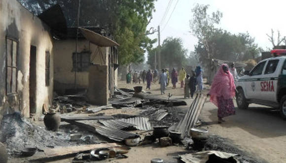 People walk past burnt houses after Boko Haram attacks at Dalori village on the outskirts of Maiduguri in northeastern Nigeria on January 31, 2016. Around 50 people were killed when Boko Haram fighters armed with guns and explosives attacked a village in northeastern Nigeria, medics and local residents said on on January 31. Nigeria's army said the gunmen attacked Dalori just outside the northern city of Maiduguri late on January 30, burning down the village and sending residents fleeing into the bush.  / AFP / STRINGER