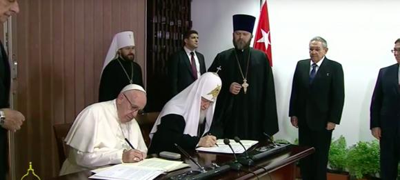 El Papa y el Patriarca sentados a la mesa firman la declaración conjunta, en presencia de Raúl Castro.