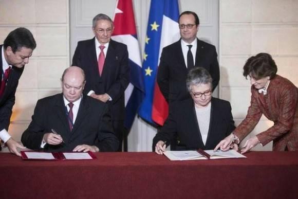 El ministro cubano de Comercio Exterior, Rodrigo Malmierca, y su par francesa, Anne Paugam, firman acuerdos comerciales, en presencia de los presidentes François Hollande y Raúl Castro, ayer en París. Foto: AFP.