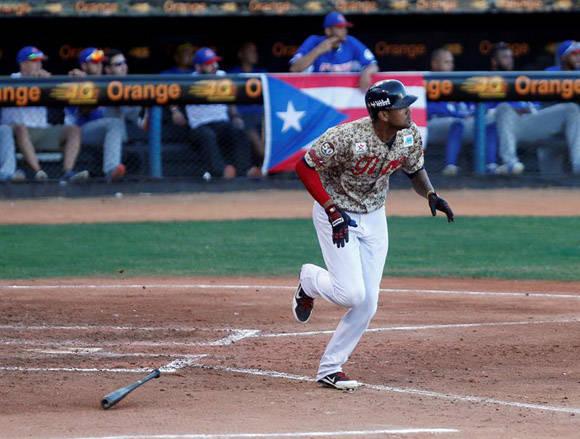 El jugador de Los Tigres de Aragua José Alberto Martínez corre a primera base después de batear ante Los Cangrejeros de Santurce. Foto: EFE.