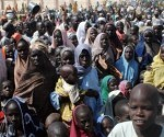 (FILES) This file photo taken on February 2, 2016 shows Internally Displaced Persons (IDP) mostly women and children waiting to be served with food at Dikwa Camp, in Borno State in north-eastern Nigeria. The death toll in a twin suicide bomb attack at a camp for people displaced by Boko Haram's Islamist insurgency has risen to 58, emergency services officials said on February 10. The Borno state emergency management agency had earlier said it recovered 35 bodies from the attack, which happened in Dikwa, some 90 kilometres (55 miles) from the city of Maiduguri, on February 9 morning. / AFP / STRINGER